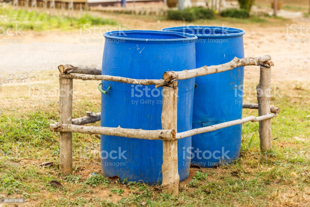 Two Blue Trash bins  in wooden fence stock photo