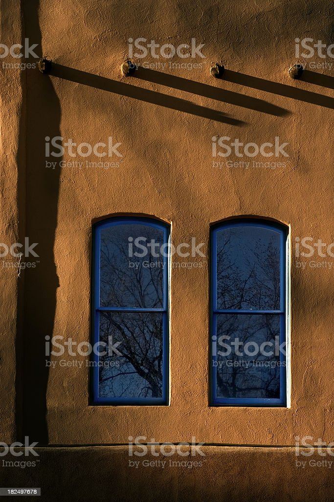 Two Blue Windows warm Adobe Walls Santa Fe New Mexico royalty-free stock photo