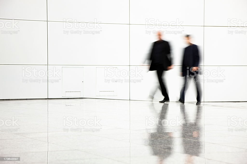 Two blurred businessmen walking in hallway royalty-free stock photo