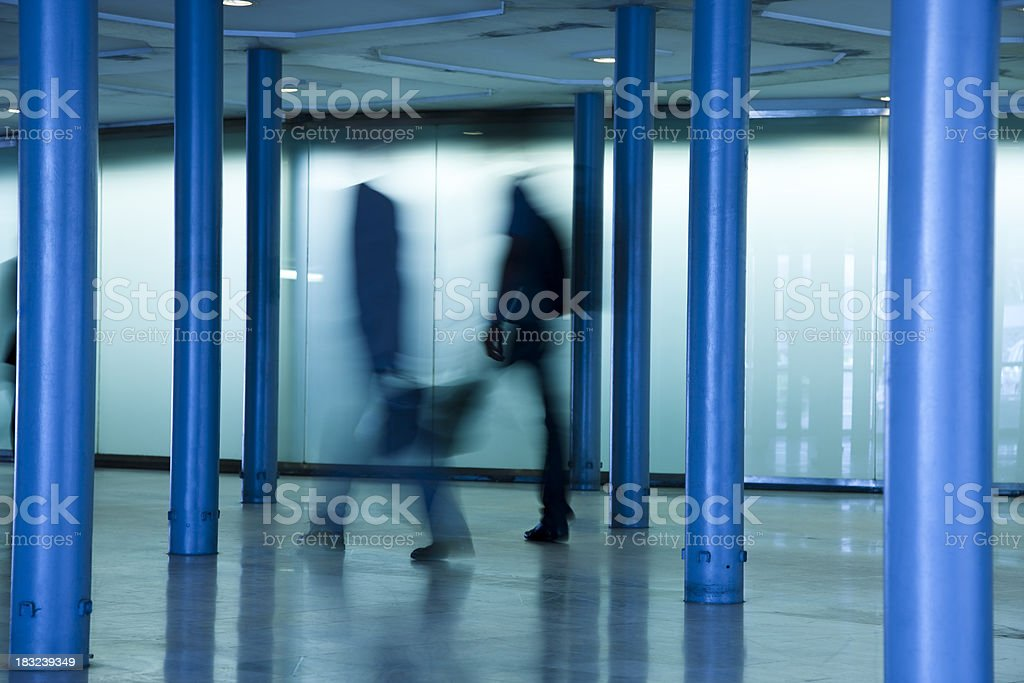 Two Blurred Businessmen Walking Through Corridor royalty-free stock photo