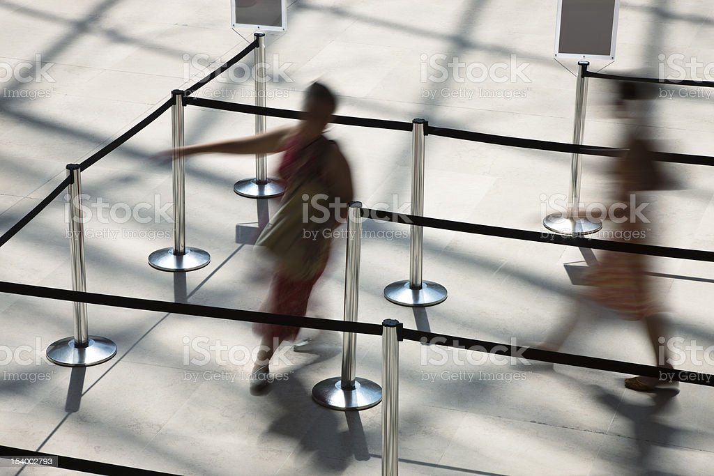 Two Blurred Women Walking Through Waiting Line royalty-free stock photo