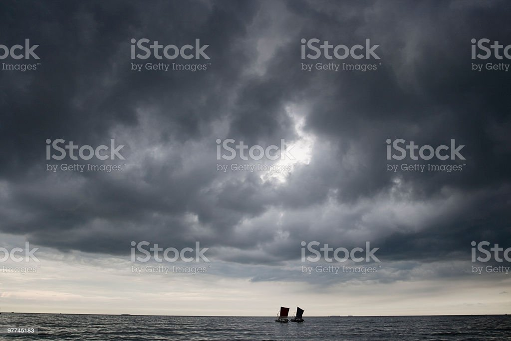 Two boats under stormy clouds at dawn. stock photo