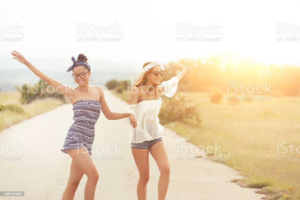 Two boho women holding hands and dancing on the road stock photo