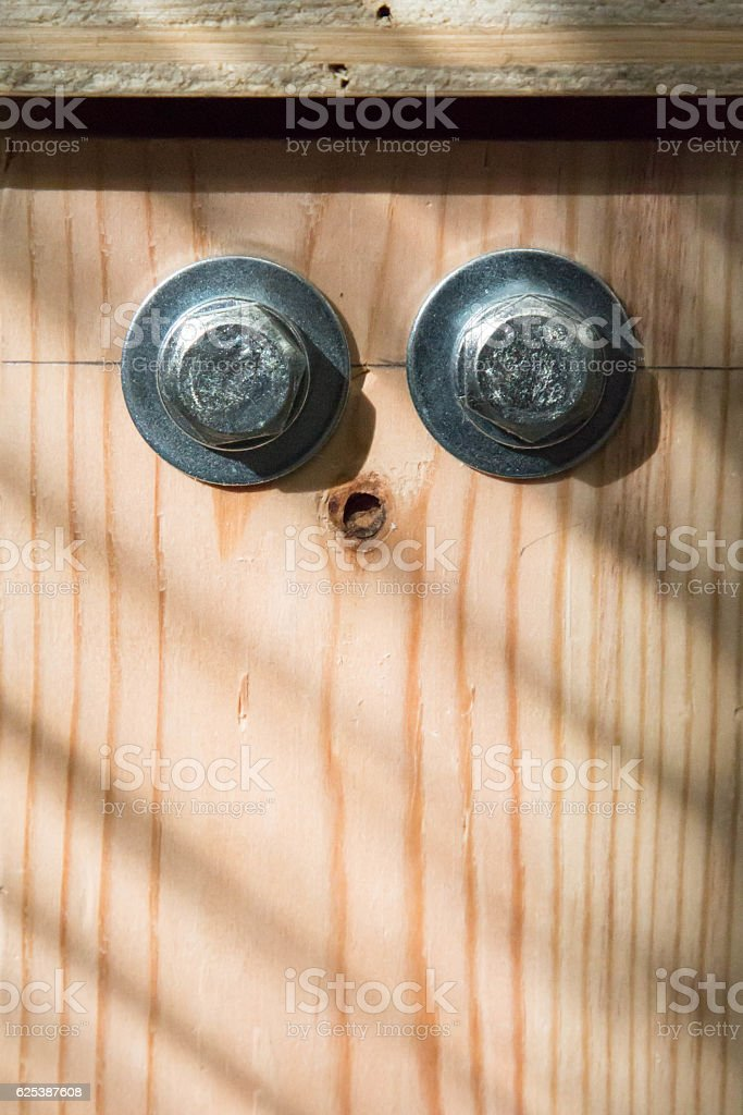 Two bolts in wood with striped shadow stock photo