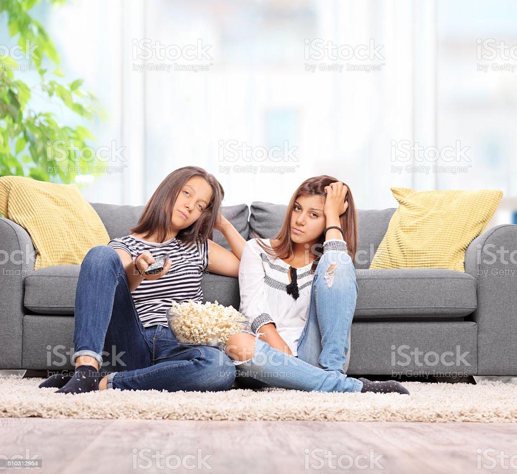 Two bored teenage girls watching TV stock photo