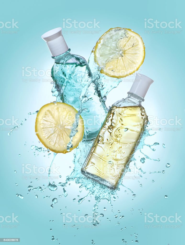 Two bottles of cosmetic  lotion in the big water splash. stock photo