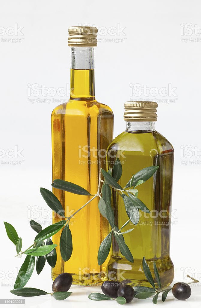 Two bottles of olive oil with fresh olives on white surface royalty-free stock photo