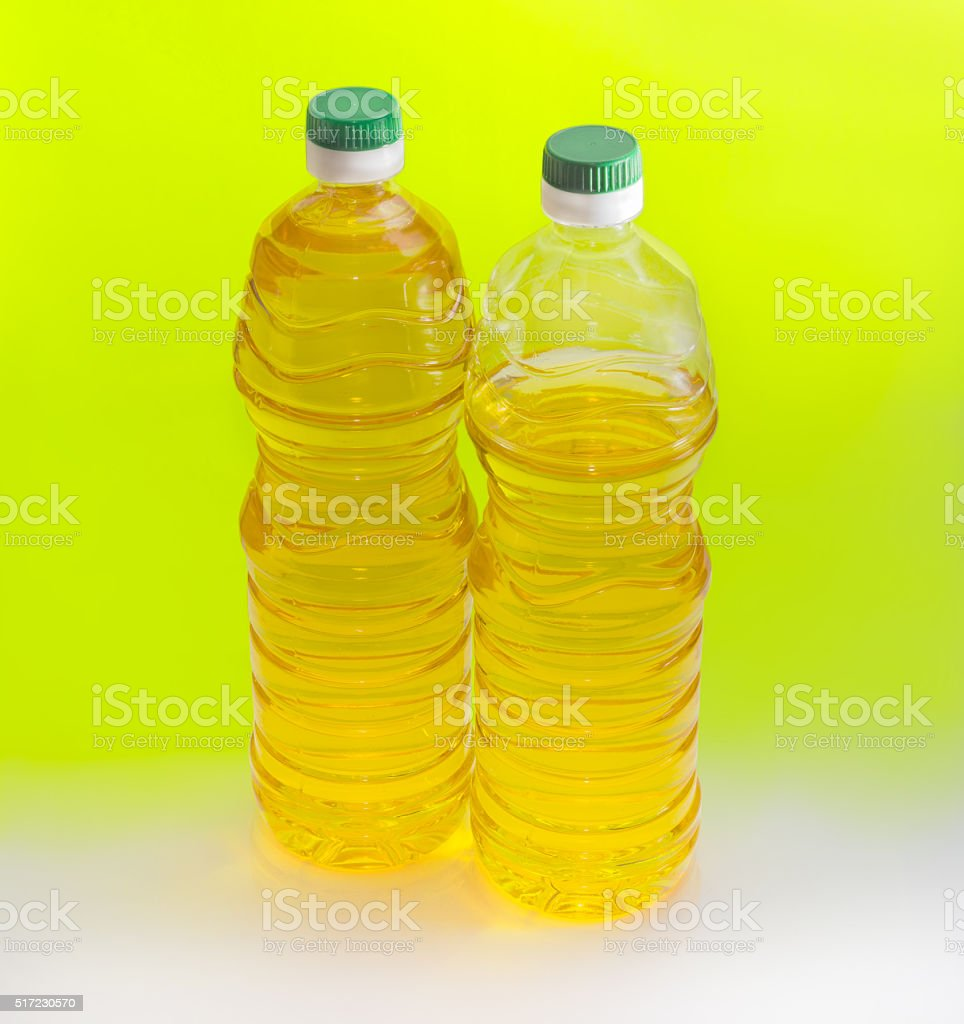 Two bottles of sunflower oil on an yellow background stock photo