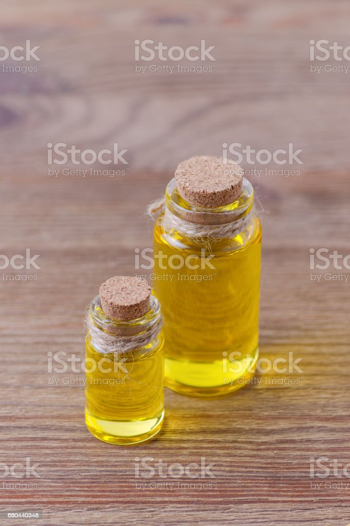 two bottles with essential oil on wooden table stock photo