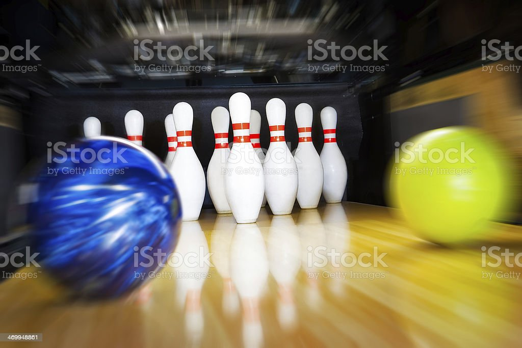 Two bowling balls approaching pins with motion blur effect stock photo