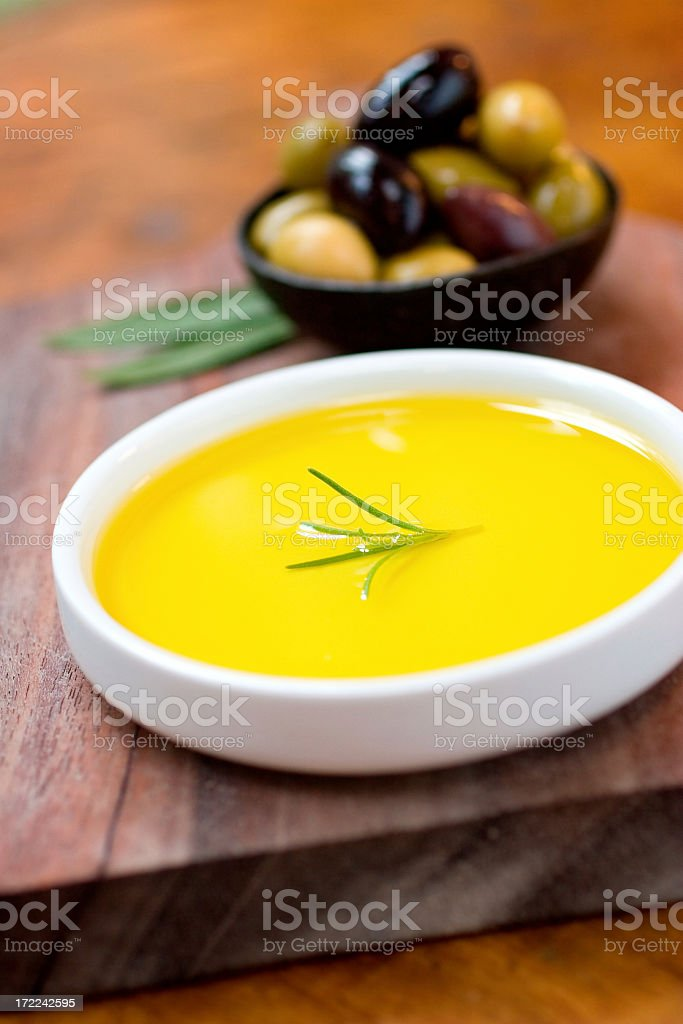 Two bowls of olives and olive oil sitting on a wood surface stock photo