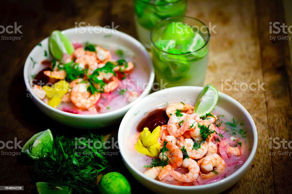 Two bowls of shrimp ceviche with wedges of lime stock photo