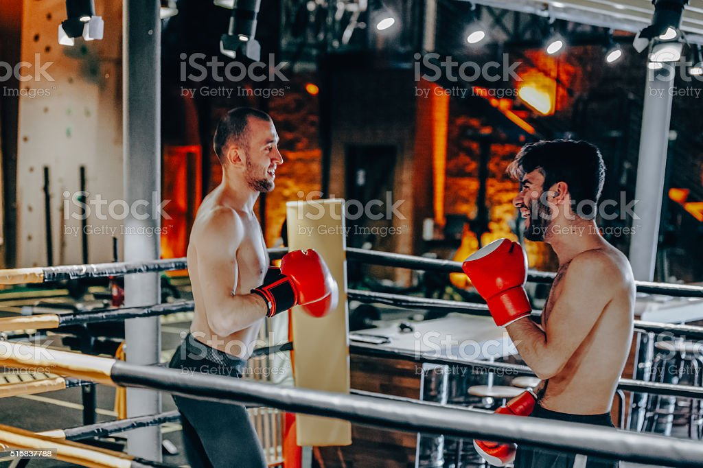 Two boxers exercising from behind ropes stock photo
