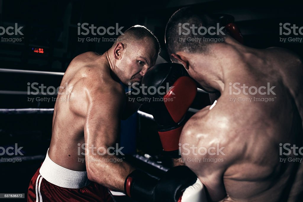Two boxers fighting in a boxing ring stock photo