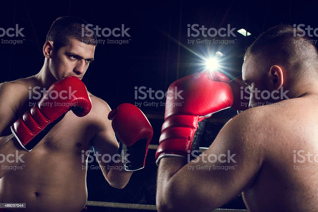 Two boxers in boxing ring ready to fight. stock photo