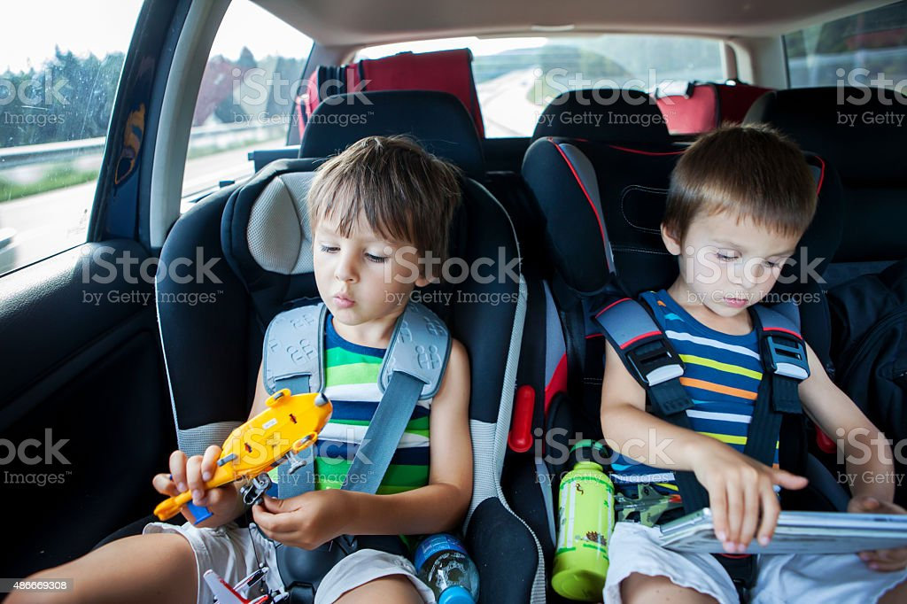 Two boy in car seats, traveling in car and playing stock photo