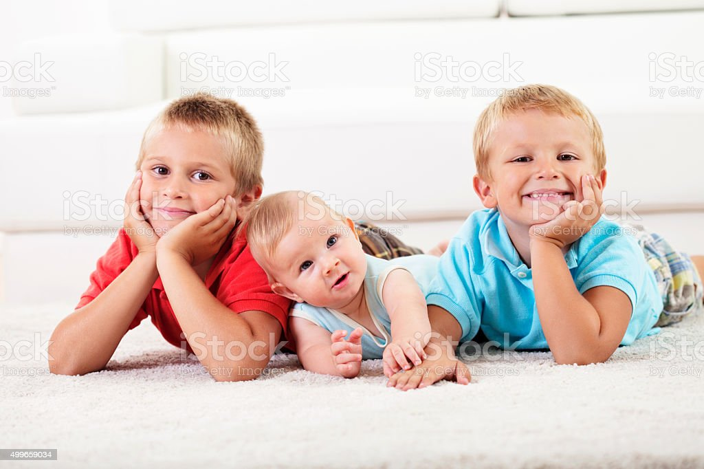 Two boys and a baby lying down on carpet stock photo