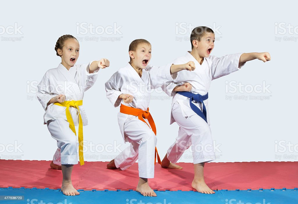 Two boys and a girl are hitting punch hand forward stock photo