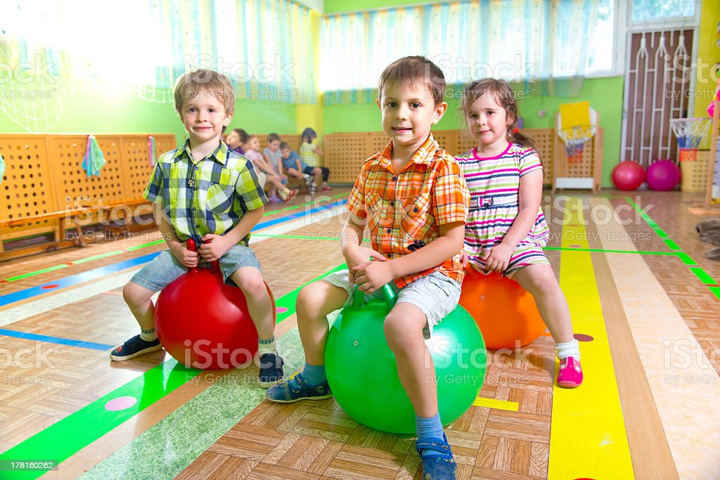 Two boys and a girl playing on bouncy balls in gym royalty-free stock photo