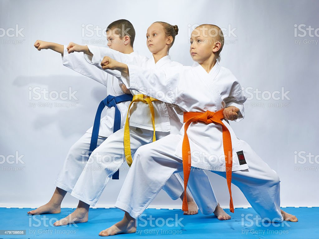 Two boys and girl in karategi are hitting punch arm stock photo
