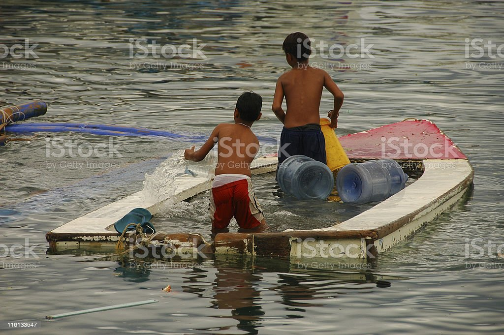 Two boys baling out boat royalty-free stock photo