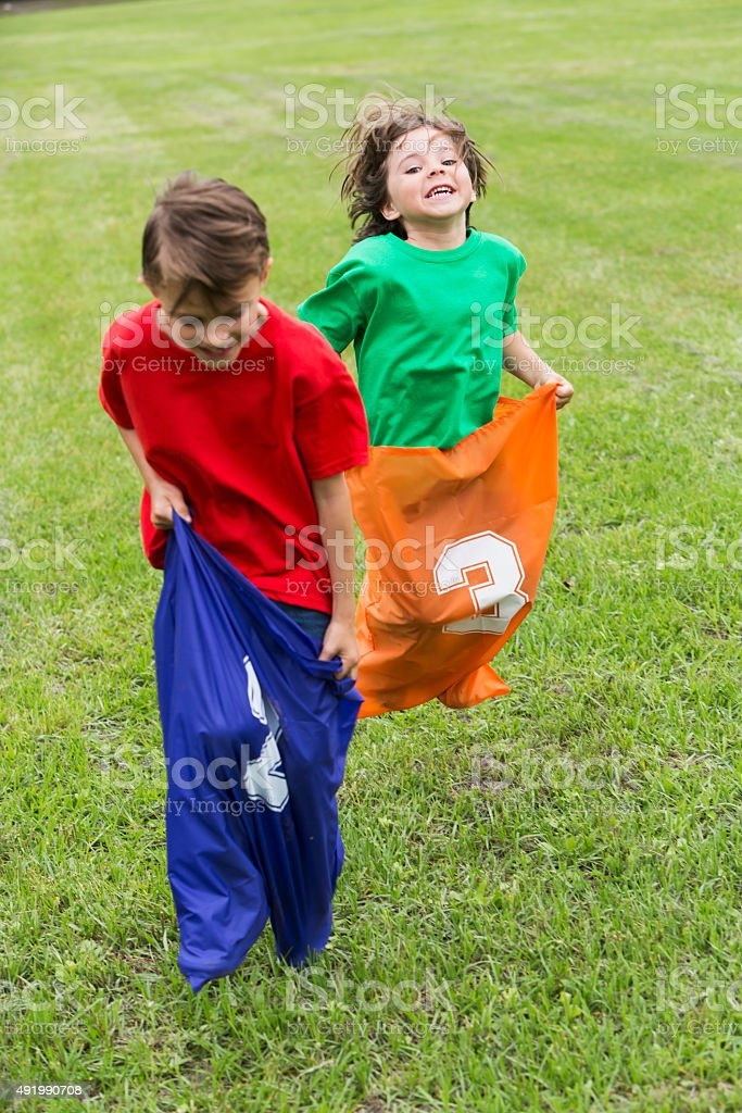 Two boys competing in a potato sack race stock photo