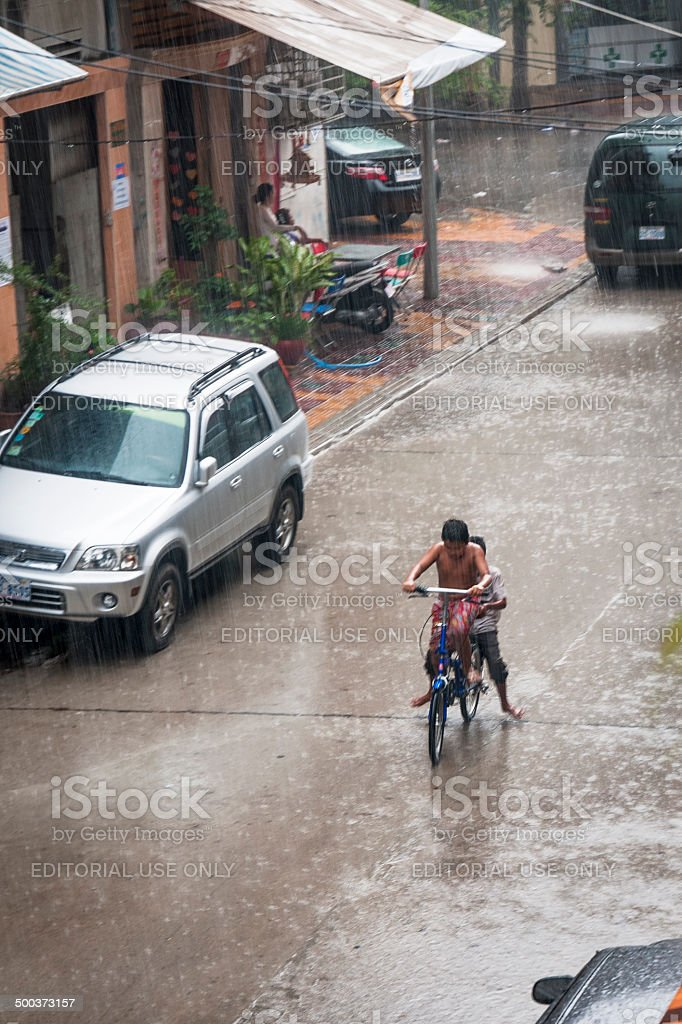 Two Boys Cycling In The Pouring Rain royalty-free stock photo