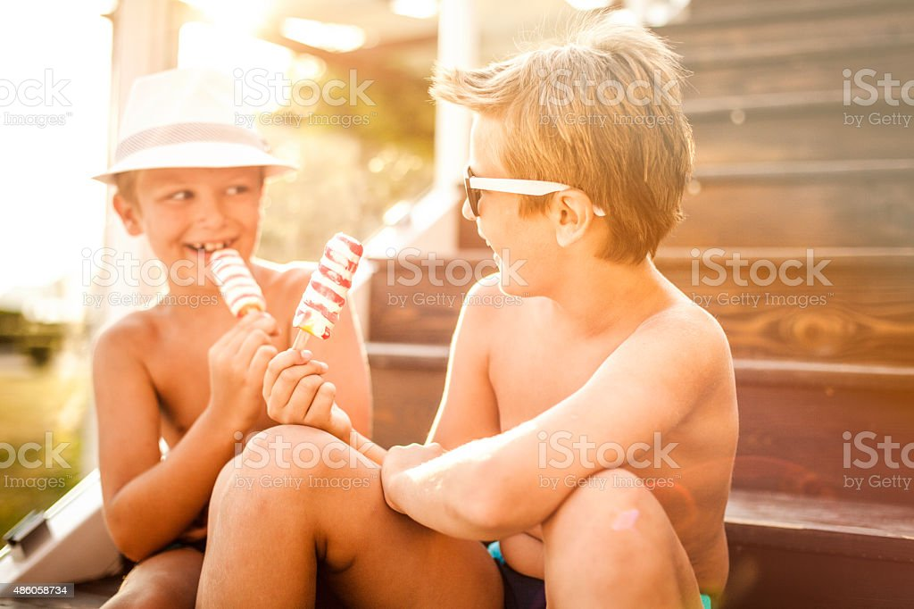 Two boys eating ice cream outdoors stock photo