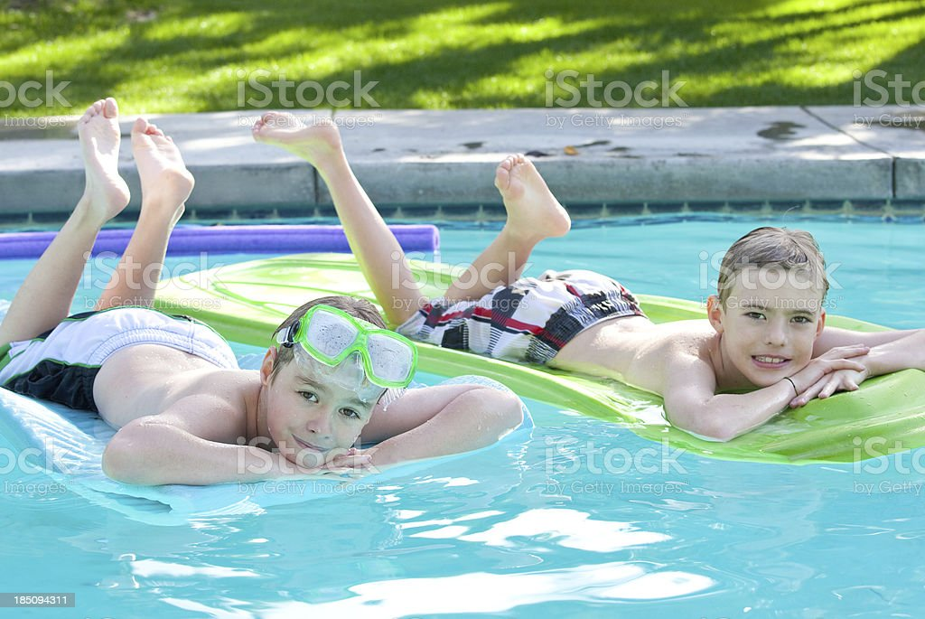 Two Boys Floating In Swimming Pool royalty-free stock photo