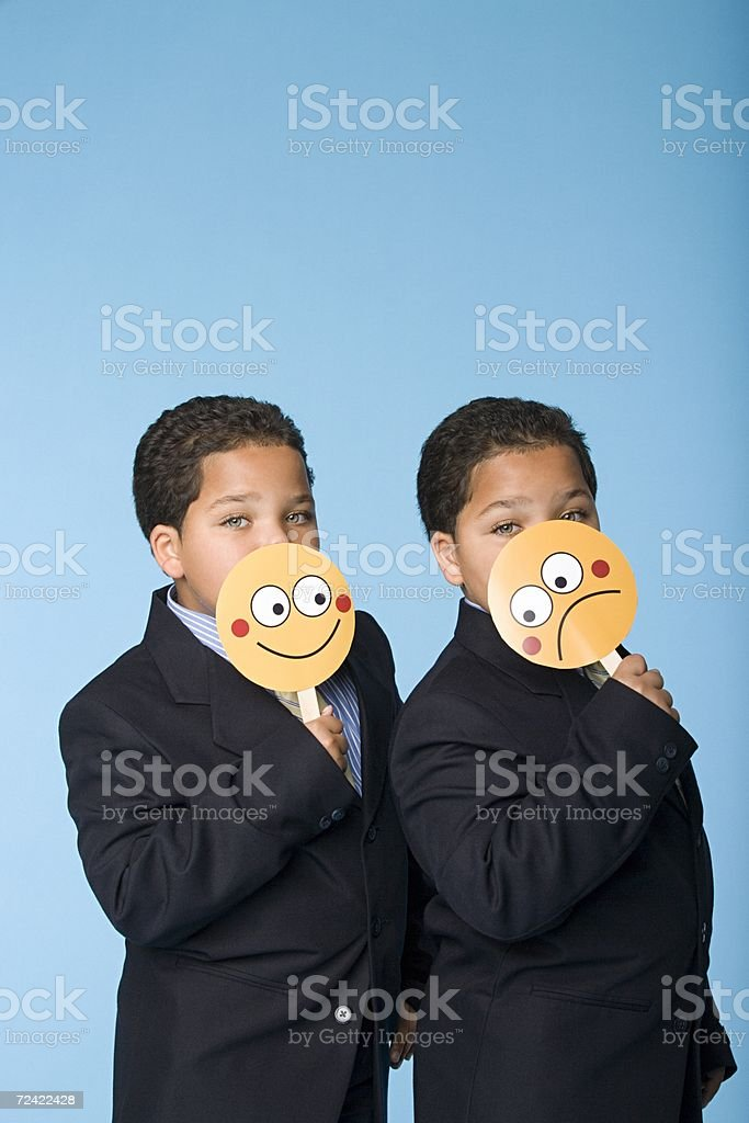 Two boys in suits holding masks royalty-free stock photo