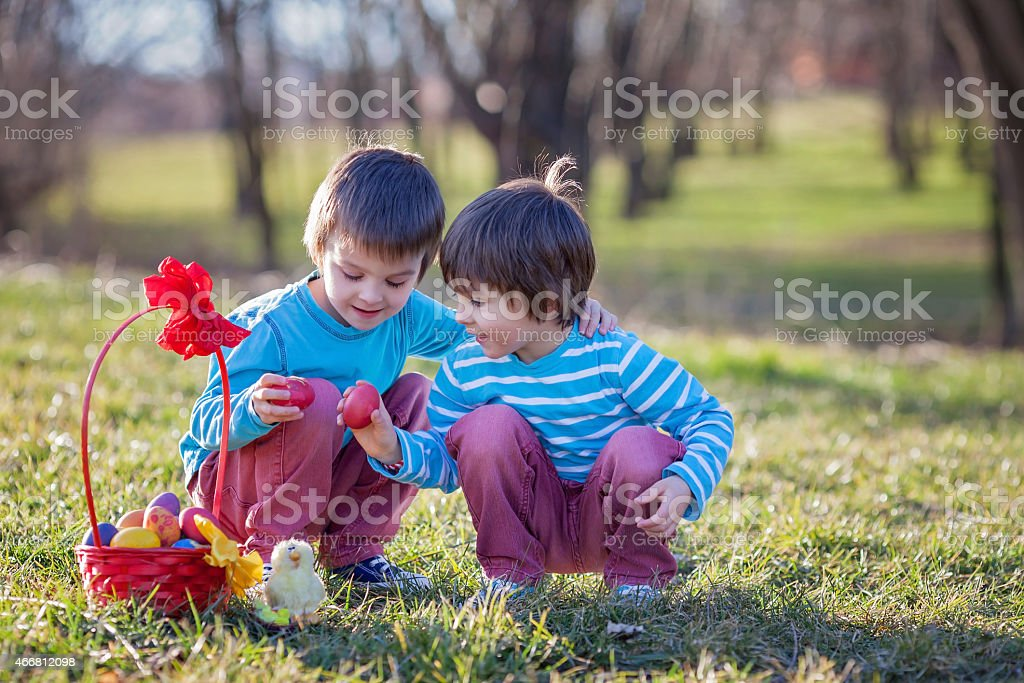 Two boys in the park, having fun with colored eggs stock photo