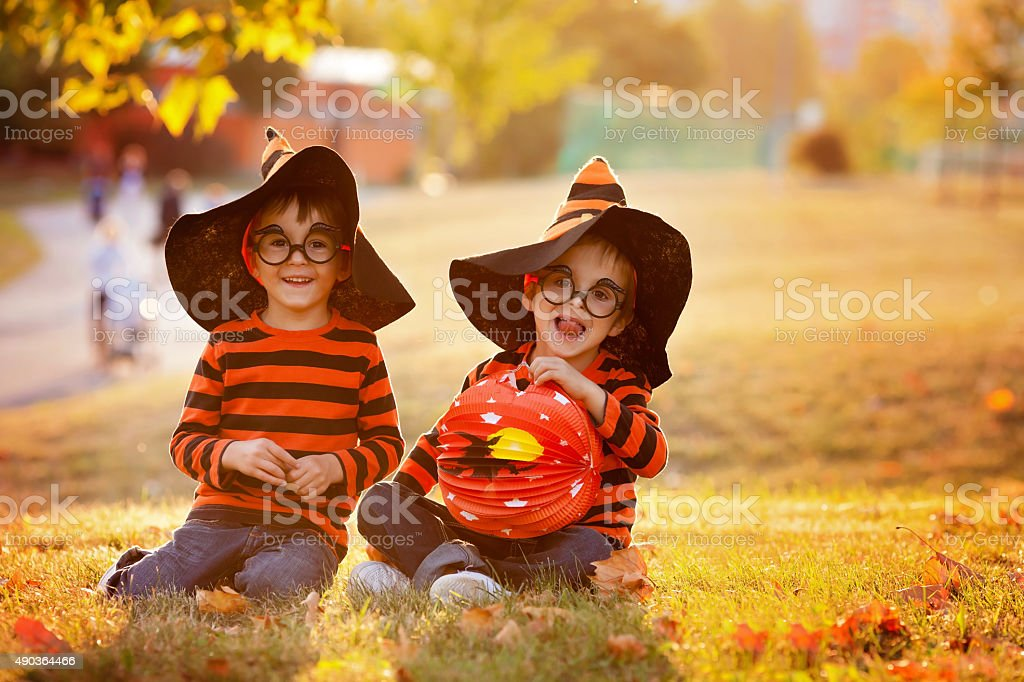 Two boys in the park with Halloween costumes stock photo