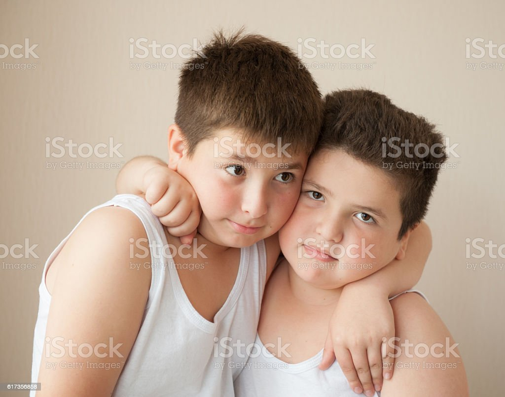 two boys in t-shirts hugging stock photo