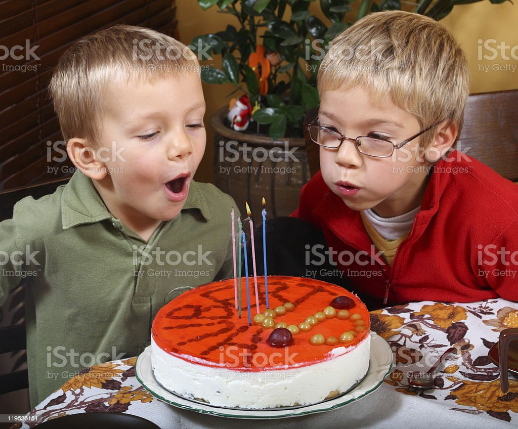 Two boys is blowing candles stock photo