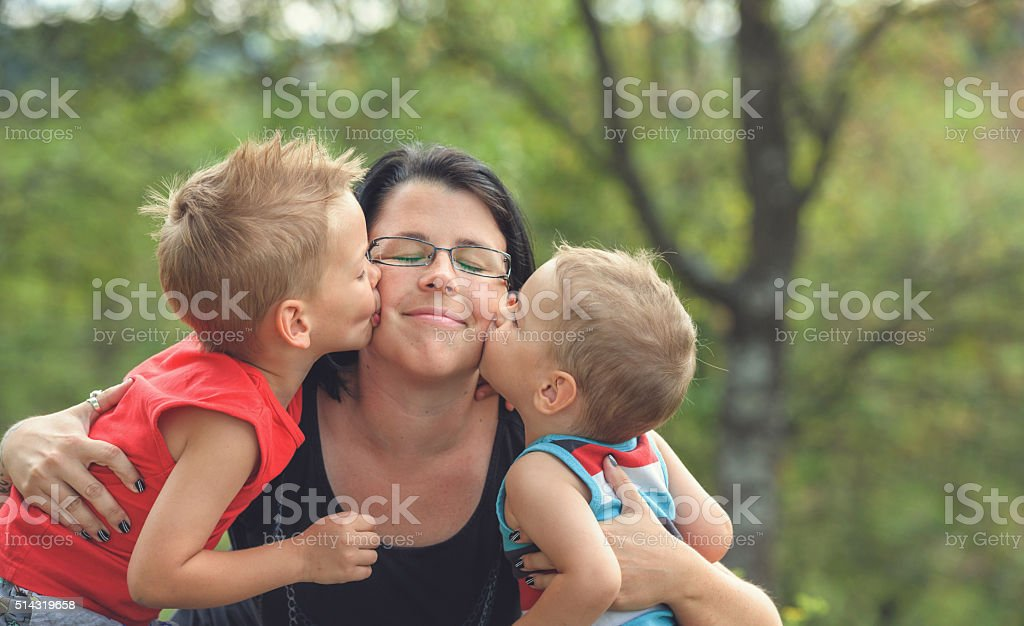 Two boys kissing mother stock photo