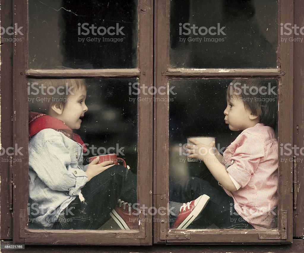 Two boys on the window, laughing, drinking tea, having fun stock photo