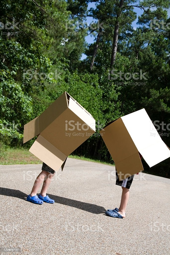 Two boys outside in road with large boxes over bodies stock photo