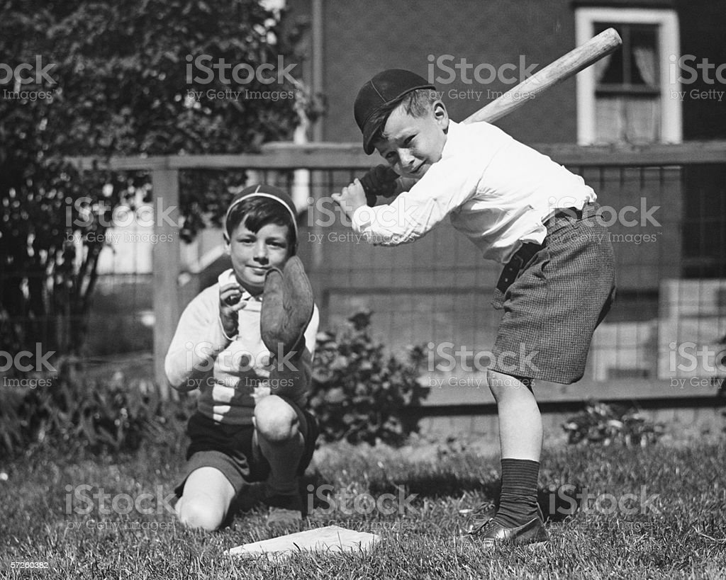 Two boys (6-7) playing baseball in garden, (B&W) royalty-free stock photo