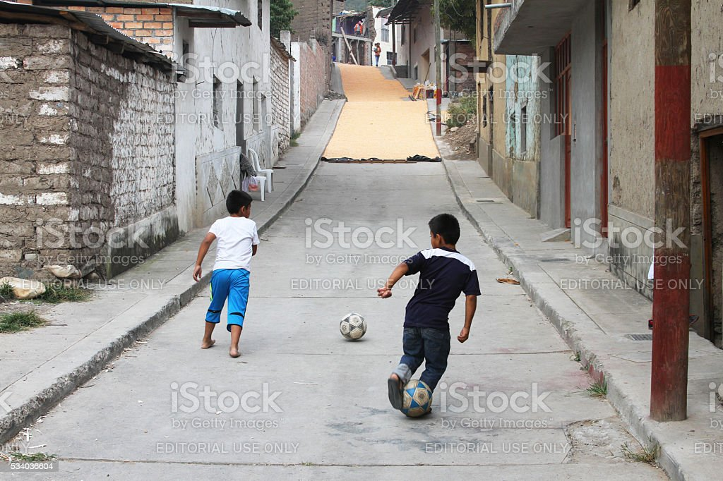 Two Boys Practice Soccer in Front of Drying Corn in Street stock photo