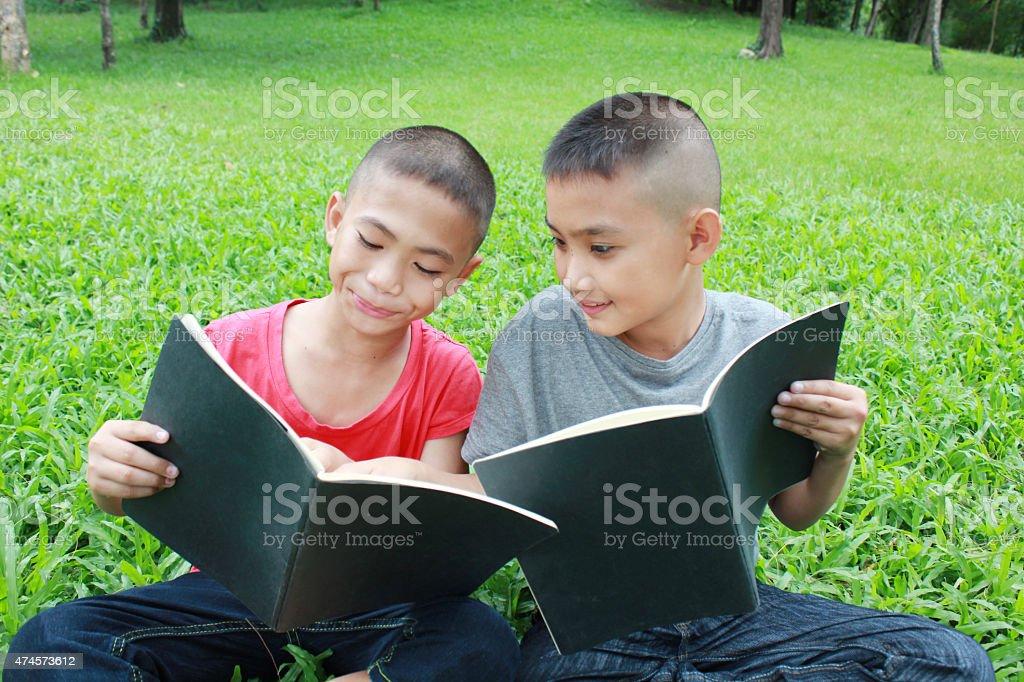 Zwei Jungen lesen im park. Lizenzfreies stock-foto