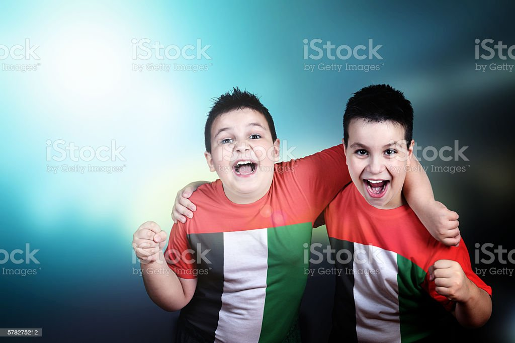 Two boys soccer fans with flag of UAE on t-shirt stock photo