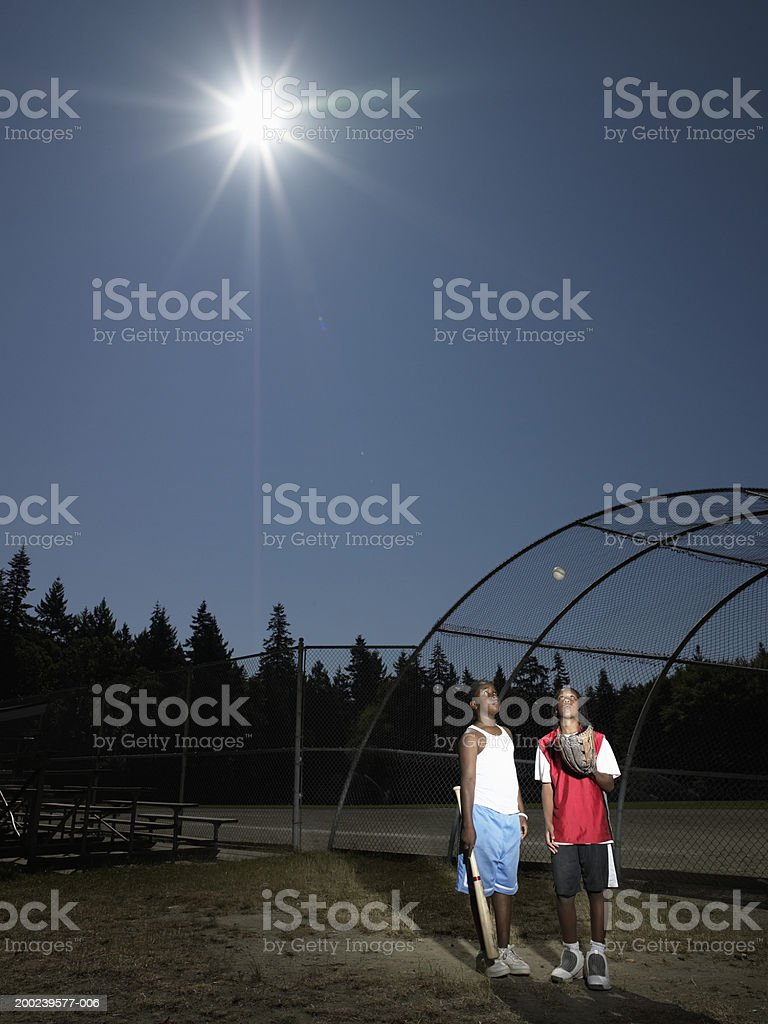 Two boys (10-12) standing beside baseball field, looking up at ball royalty-free stock photo