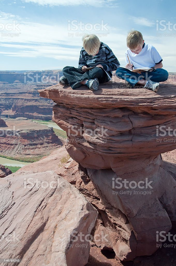 Two Boys Study On Top of Red Rock royalty-free stock photo