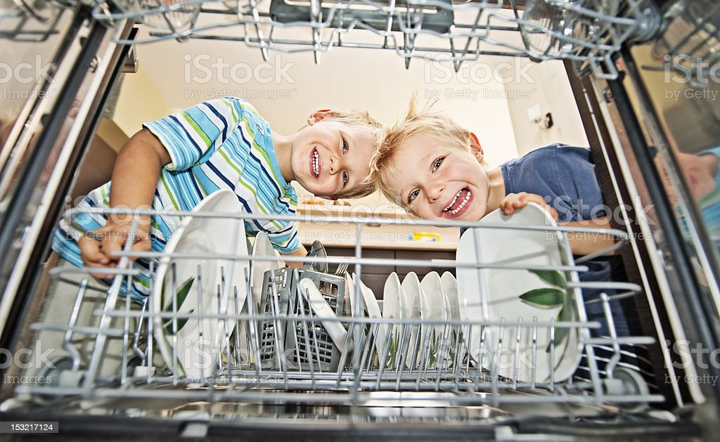 Two boys unloading a dishwasher royalty-free stock photo