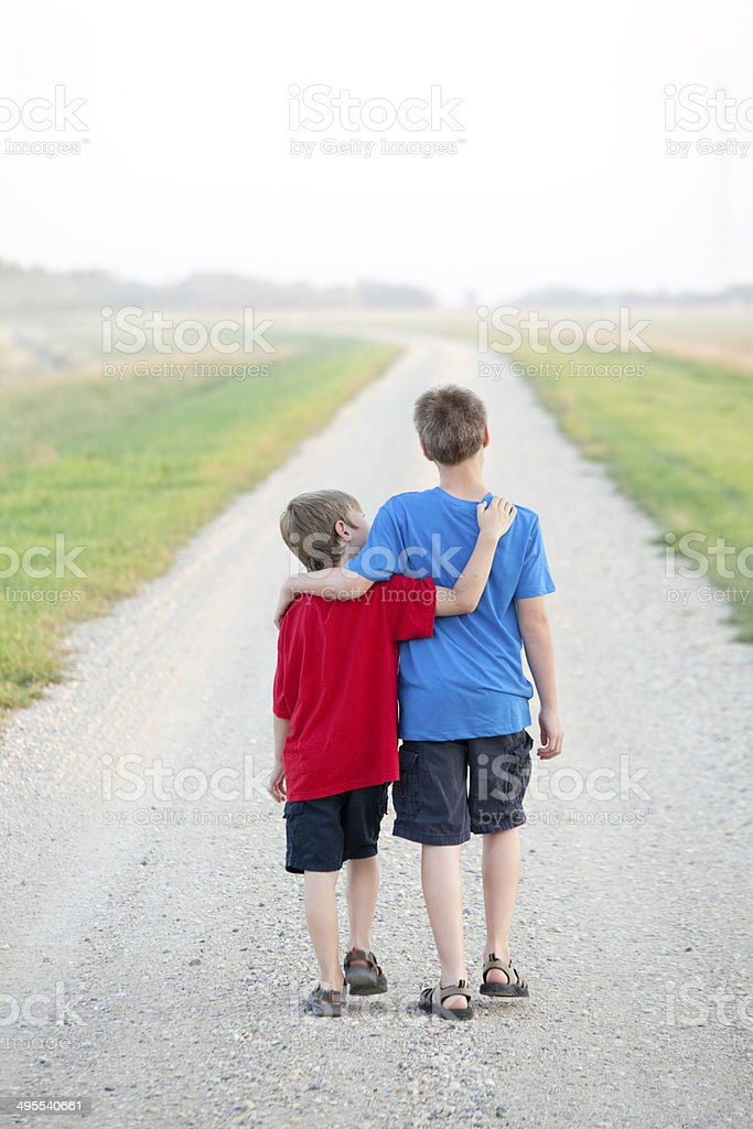 Two Boys Walking Down a Country Road stock photo