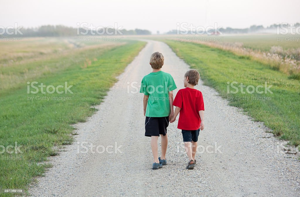 Two Boys Walking Down a Country Road royalty-free stock photo