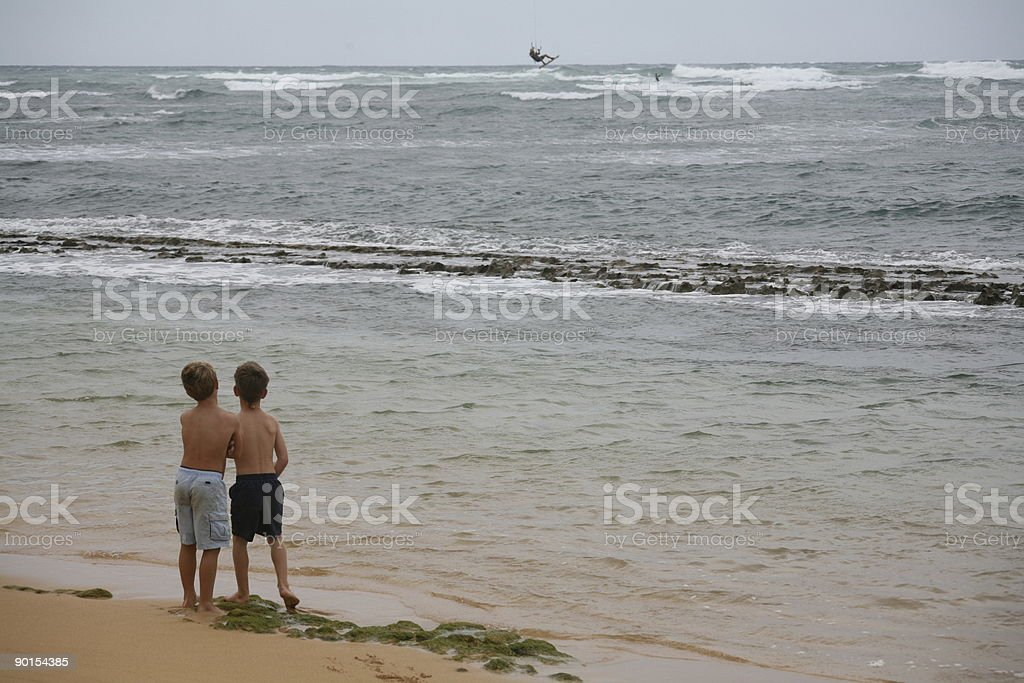 Two boys watching kite surfer in distant royalty-free stock photo