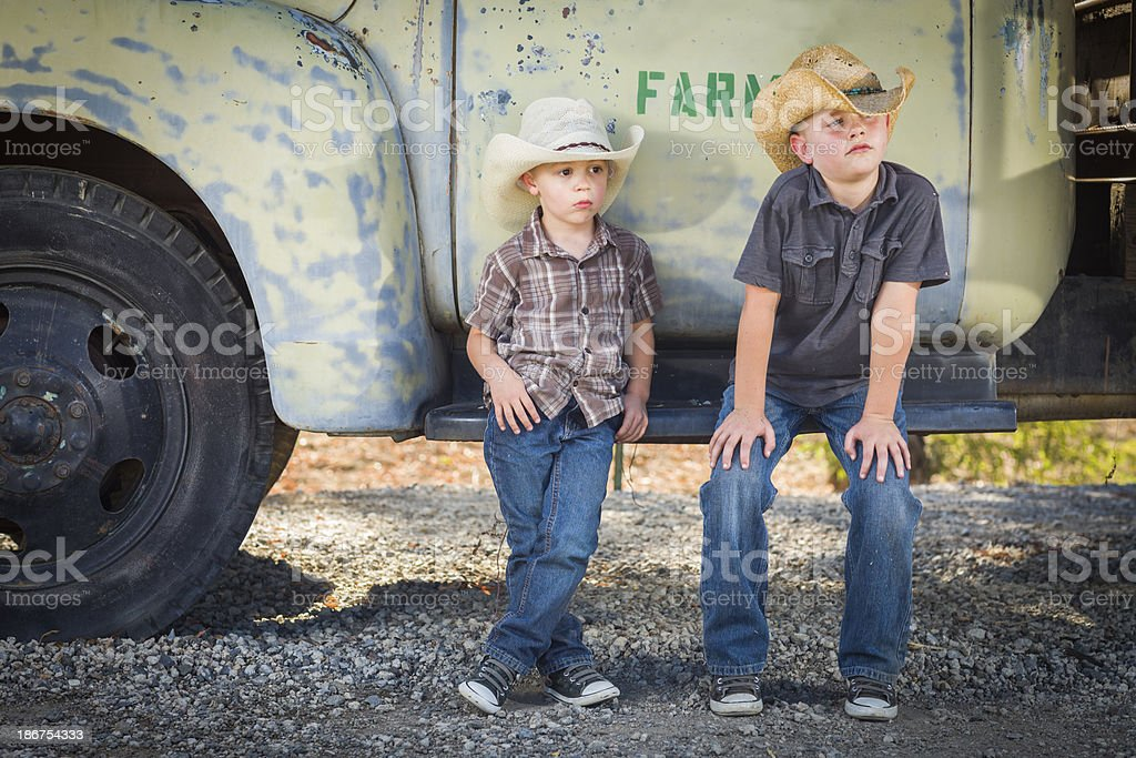 Two boys wearing cowboy hats sitting on an antique truck royalty-free stock photo