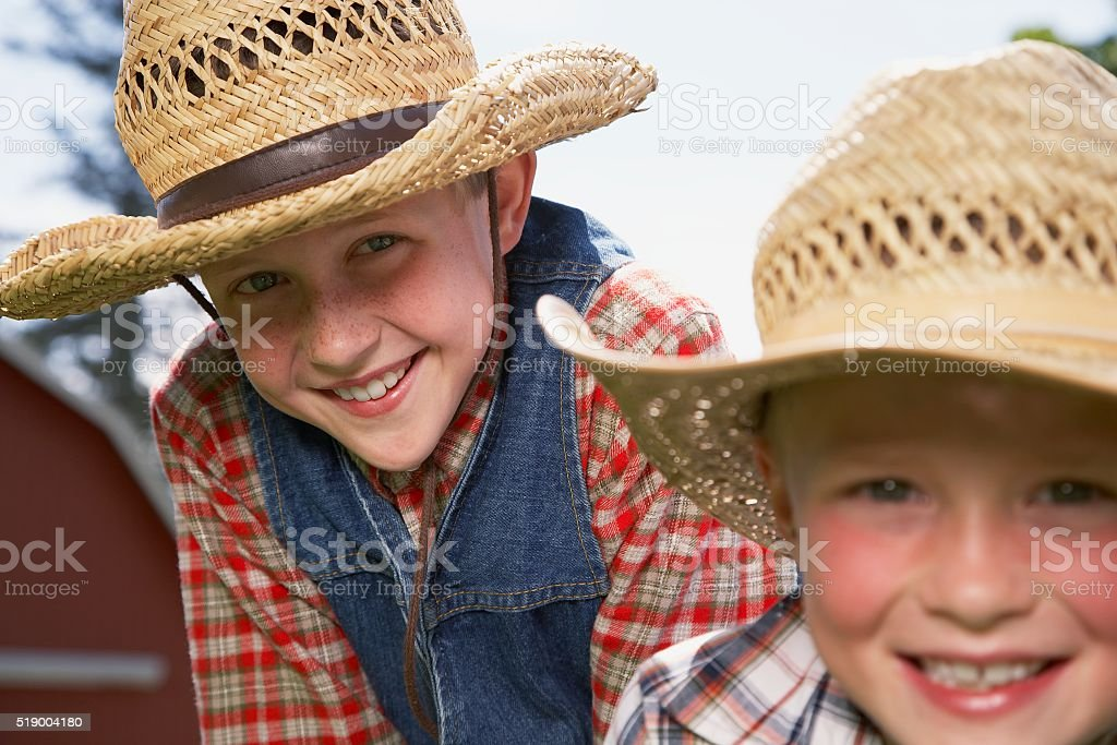 Two boys wearing straw hats stock photo