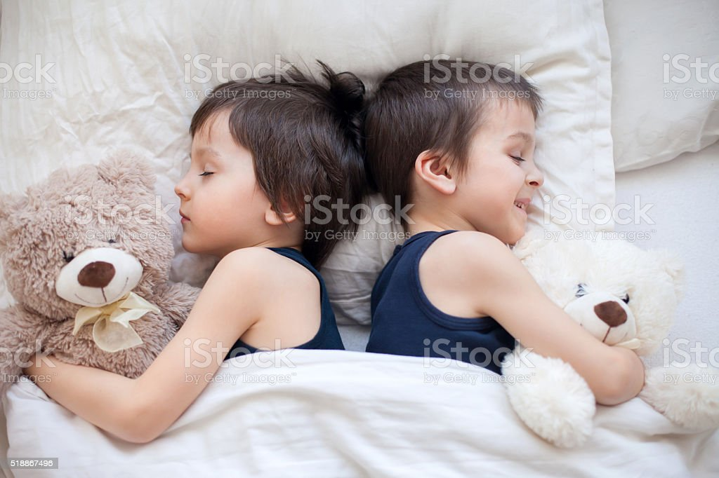 Two boys with teddy bears, lying in bed, sleeping stock photo